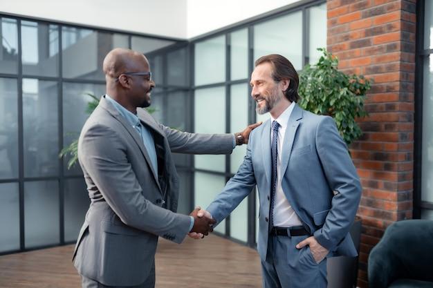 웃는 투자자. 그의 비즈니스 파트너를 만나면서 웃고 있는 아프리카계 미국인 투자자