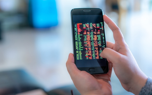 Investor trading stocks on smart phone