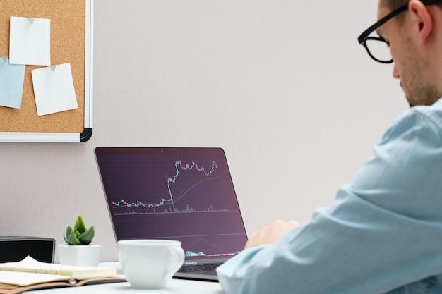 ノートブックで株式市場の変化を見ている投資家