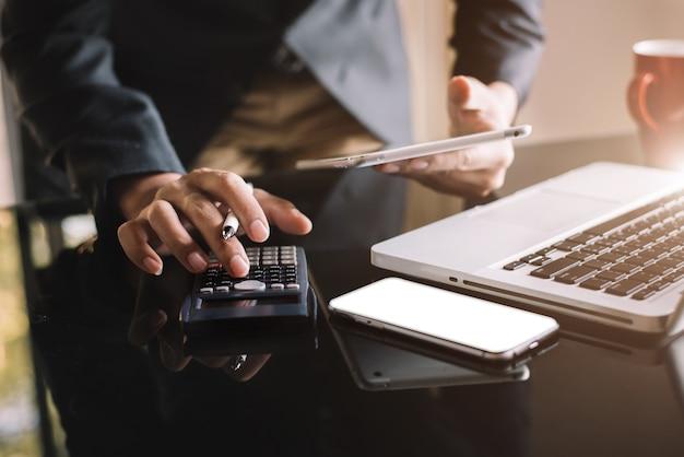 Инвесторы рассчитывают инвестиционные затраты на калькуляторе и держат в руках планшет и компьютер в домашнем офисе.