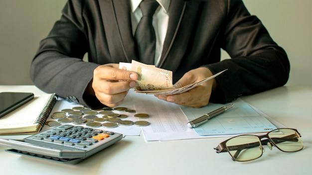 投資家は紙幣を数え、投資コスト、財務アイデア、investments.softフォーカスを計算しています。