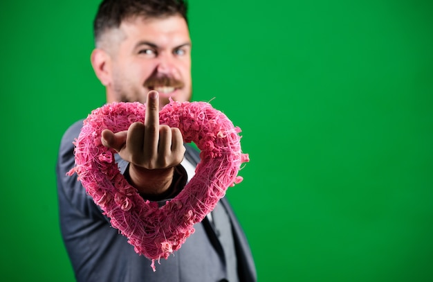 熱心な独身者。バレンタインデーの休日。装飾的な心を持つスタイリッシュなエステ。フォーマルなスーツを着たひげを生やした男。愛。結婚式の日。蝶ネクタイの実業家。コピースペース。男は中指を表示します。