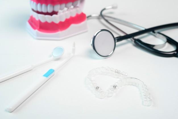 歯科治療、歯科医療、歯科矯正の概念のためのインビザラインブレースとツール。
