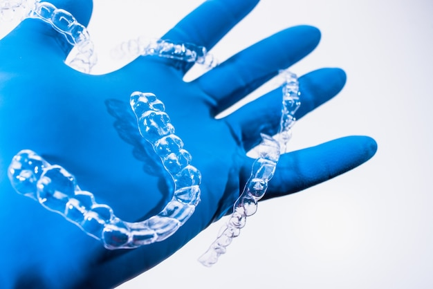目に見えない歯列矯正器は、白い背景の上の青い手袋で手で保持されます。プラスチック製のブレース歯科用リテーナーで歯を矯正します。