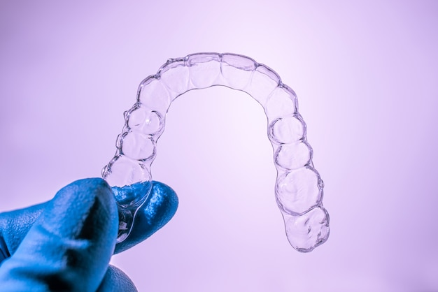 Invisible dental braces are held by a hand in a blue glove on a purple background. plastic braces dentistry retainers to straighten teeth.