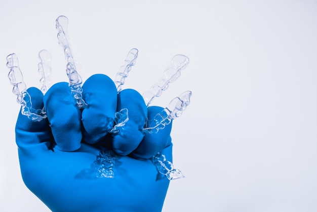 Invisible dental braces are held by a hand in a blue glove on a white background. plastic braces dentistry retainers to straighten teeth.