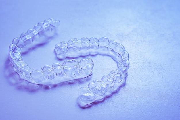 Невидимые зубные скобки зубные выравниватели на синем фоне. пластиковые брекеты, ретейнеры для стоматологии, для выпрямления зубов.