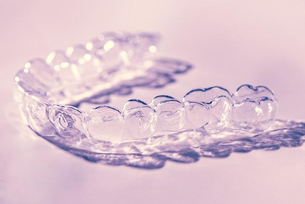 보이지 않는 치과 치아 브래킷 치아 정렬 기. 플라스틱은 치아를 곧게 펴기 위해 치과 용 리테이너를 교정합니다.