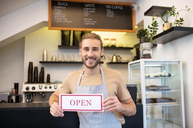 招待状、カフェ。訪問者を招待する彼のオープニングカフェのカウンターの近くに立っているtシャツとエプロンの満足した男