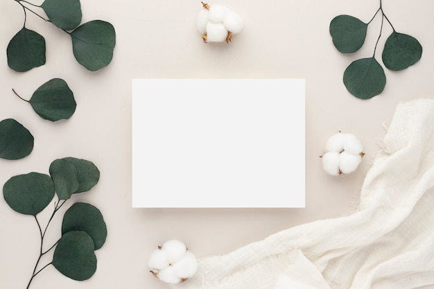 Invitation card mockup with eucalyptus branch on beige background, . flat lay, top view with copy space