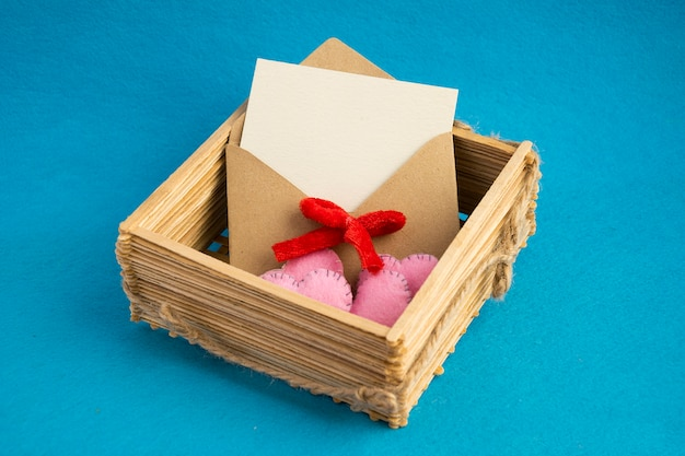 Invitation envelope in wooden wicker basket decorated with pink hearts isolated on blue