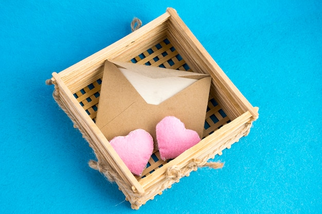 Invitation or love letter in old wooden wicker with plush hearts on blue