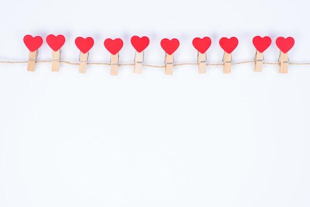 Сообщение приглашения на день святого валентина концепции. фотография красивой прекрасной мечты милые прищепки, вручая веревку, изолированный белый цвет фона