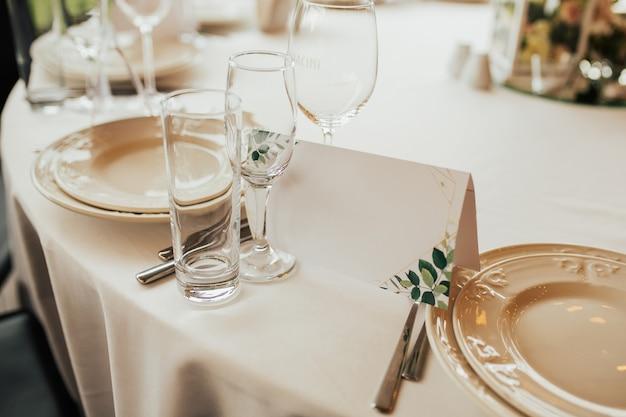 コピースペースのあるプレートの近くの招待状。パステルカラーのテーブルクロスに白いプレート。結婚披露宴のための美しいテーブルデコレーション。