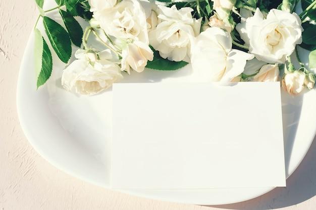 Приглашение или открытка на фоне белой тарелки с букетом розовых цветов
