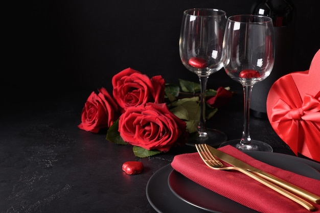 Приглашение на ужин в день святого валентина. сервировка праздничного стола с романтическим подарком, красные розы на черном. открытка с копией пространства.