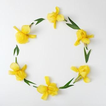 테두리와 화환이 있는 초대장에는 노란색 밝은 색상의 아이리스 꽃 장식이 있습니다. 최소한의 장식 배너 아이디어입니다.