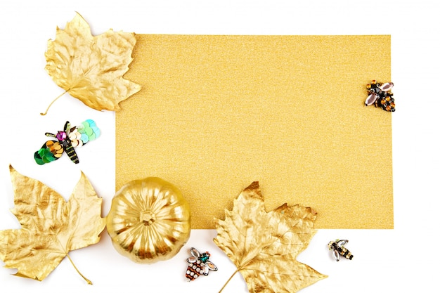 Invitation with golden pumpkin and party objects, bats, overhead view