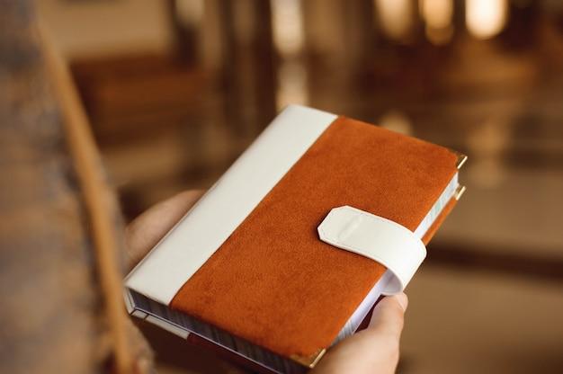 Приглашения, блокнот, блокнот ручной работы в руках.