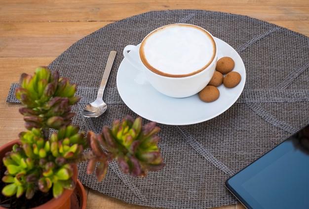 木製のテーブルのわらのプレースマットにミルクの泡と焼きたてのクロワッサンが入ったカプチーノの魅力的なカップ-角に多肉植物とタブレット