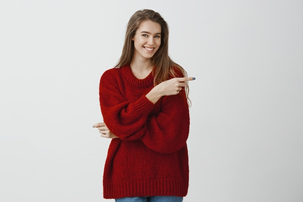 Приглашение друзей на чашку чая. портрет уверенно симпатичной кавказской женщины-фрилансера в свободном свитере, указывающей вправо указательным пальцем и улыбающейся с одобрением, любящей идею над серой стеной