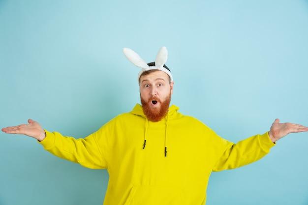 Приглашение, приветствие. кавказский человек как пасхальный кролик с яркой повседневной одеждой на синем фоне студии. поздравления с пасхой. понятие человеческих эмоций, выражения лица, праздников. copyspace.