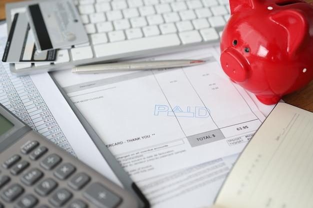 オフィスコンセプトのテーブル書類に銀行カードと貯金箱の支払いスタンプ付きの請求書
