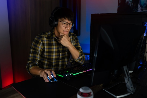 Involved asian man cyber sport gamer concentrated playing video games on computer at night dark room at home, esport and technology concept