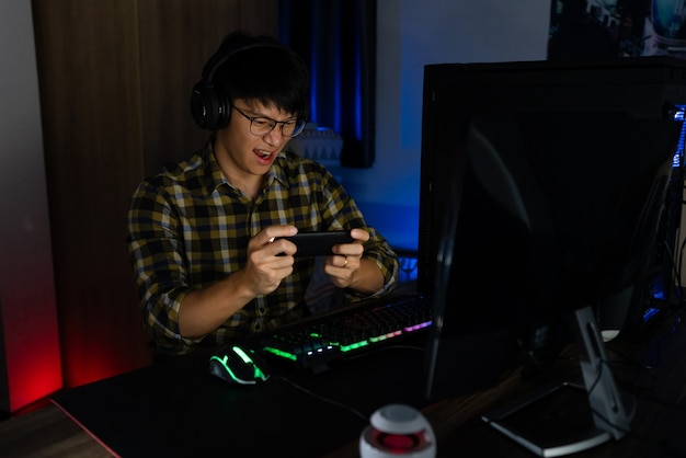 Involved asian man cyber sport gamer concentrated playing video games on computer at night dark room at home, esport and technology concept.