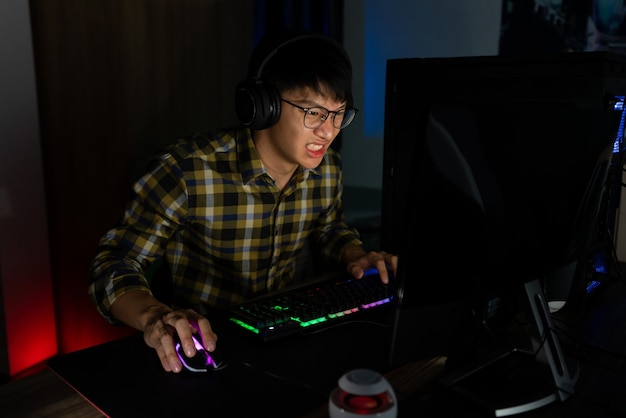 Вовлеченный азиатский человек, киберспортсмен, сосредоточился, играя в видеоигры на компьютере в ночной темной комнате дома, киберспорт и технологическая концепция.