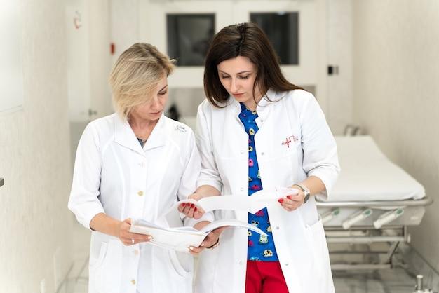 仕事に携わる。病院に立って、話し、文書を見ている2人の真面目な女性医師。仕事について話し合い、紙の上で見ている女性医師