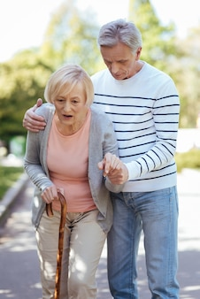 Involved caring mature man caring about his old mother and helping her to make steps while walking outdoors