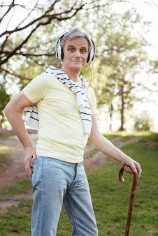 公園を散歩したり音楽を聴いたりしながら、ヘッドホンを使ってスティックに寄りかかって魅力的な老人を巻き込んだ