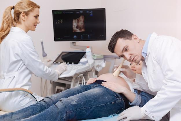 胎児の心臓の鼓動をチェックするための医療機器を使用しながら病院で働く勤勉な資格のある開業医を巻き込んだ