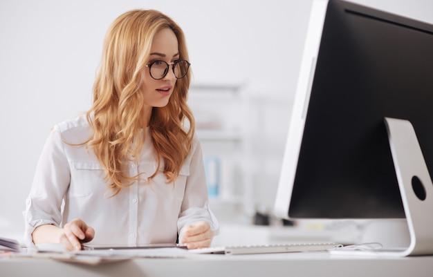 オフィスのテーブルに座って、タブレットを使用してドキュメントを読みながら作業している幸せな若い実業家を巻き込んだ