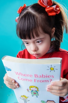 お祝いにかかわる。重要なトピックに関する教育的な本を読んでいるダウン症の黒髪の小さな子供