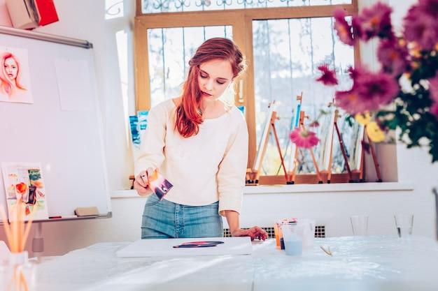 회화에 관여했습니다. 빨강 머리 젊은 재능있는 예술가가 대리석 페인팅에 관여하는 느낌