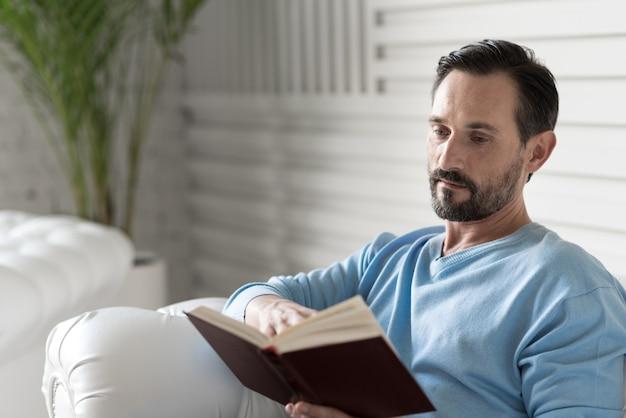 Участвовал в чтении. серьезный приятный взрослый мужчина держит книгу и переворачивает страницу, читая рассказ