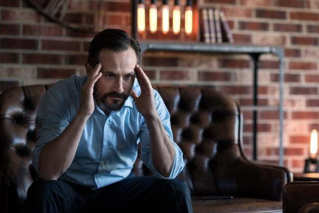 思考プロセスに関与します。ハンサムな自営業のスタイリッシュなビジネスマンがソファに座って、思考プロセスに関与しながら頭に手を置いています