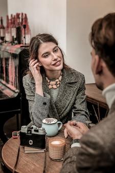 Участвует в разговоре. молодая женщина заинтересована в разговоре со своим партнером, сидя в кафе