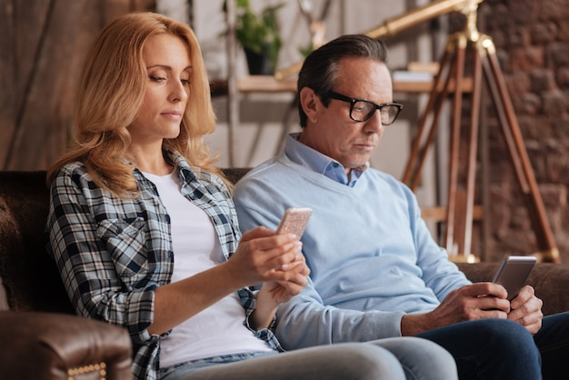 Вовлеченная зрелая запечатленная пара, сидящая на диване дома и использующая мобильные устройства во время серфинга в интернете и выражающая апатию