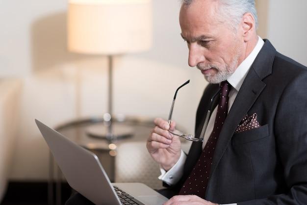노트북으로 작업하는 동안 안경을 들고 호텔에 앉아 즐거운 수염을 가진 사업가 참여