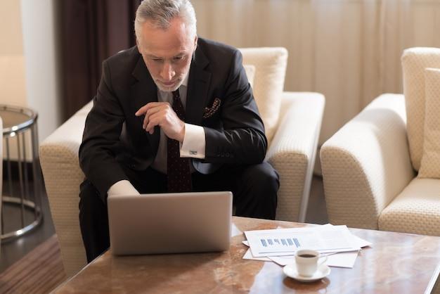 노트북으로 작업하고 집중하는 동안 호텔에 앉아 즐거운 수염을 가진 사업가 참여