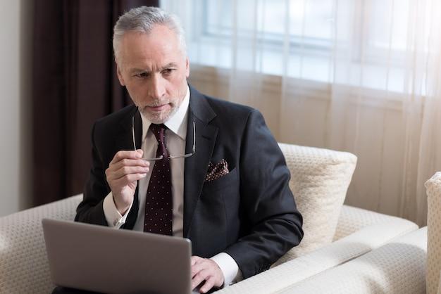 노트북으로 작업하는 동안 안경을 들고 호텔에 앉아 심각한 수염 난 사업가 관여