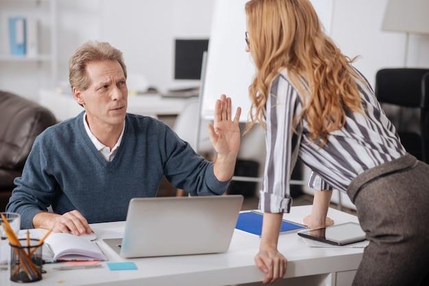 사무실에 앉아 일하는 동안 부정적인 감정을 보여주는 충격을받은 성숙한 관리자