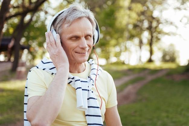 Вовлеченный улыбающийся пенсионер в наушниках, наслаждаясь погодой в парке и слушая музыку