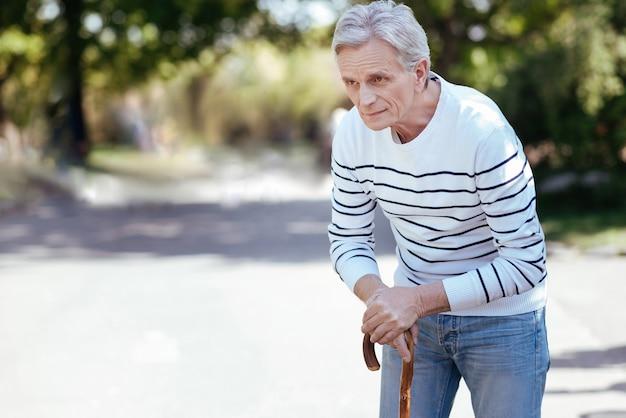 Вовлеченный задумчивый старик смотрит в сторону и опирается на палку во время прогулки в парке