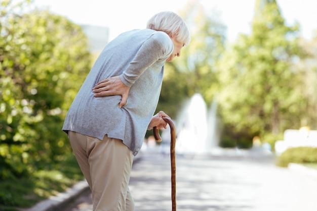 건강에 해로운 노인 여성이 등을 만지고 야외에서 요통을 겪는 동안 막대기에 기대어 포함