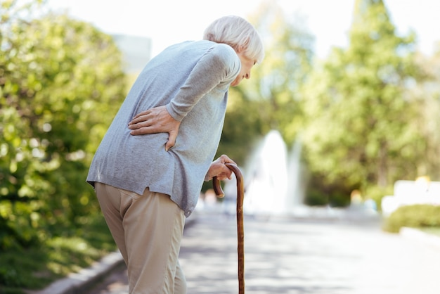 Involved unhealthy aged woman touching her back and leaning on the stick while having backache outdoors