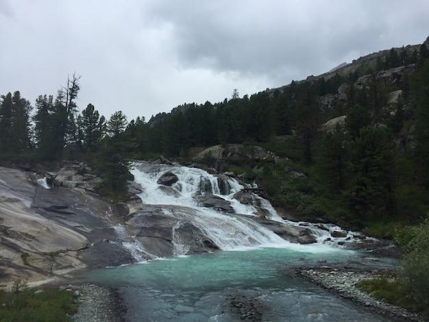 岩の間のioldo-ayry滝。青い森の滝。アルタイ山脈、シベリア、ロシア